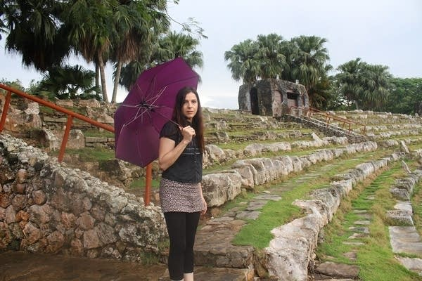 Woman with umbrella stands in ancient amphitheater.