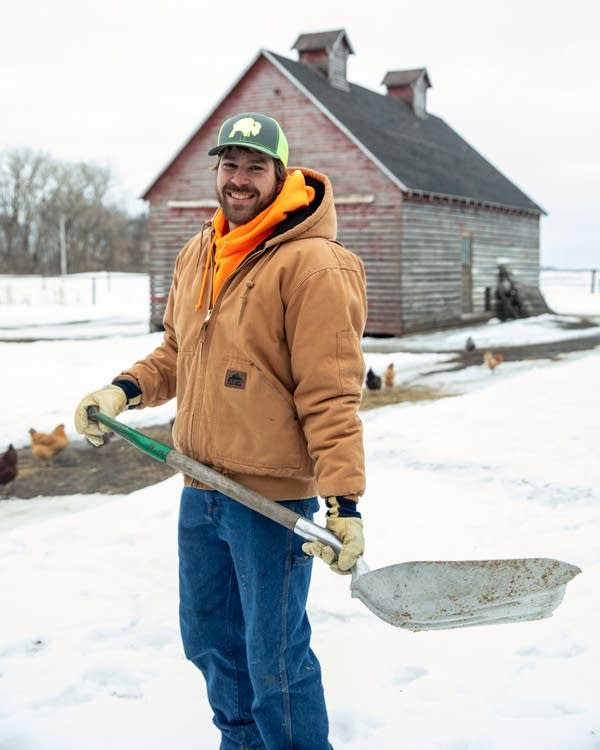 A man stands in front of a barn with a shovel.