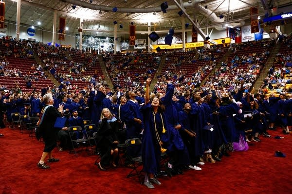 Kennedy graduates toss their caps into the air.