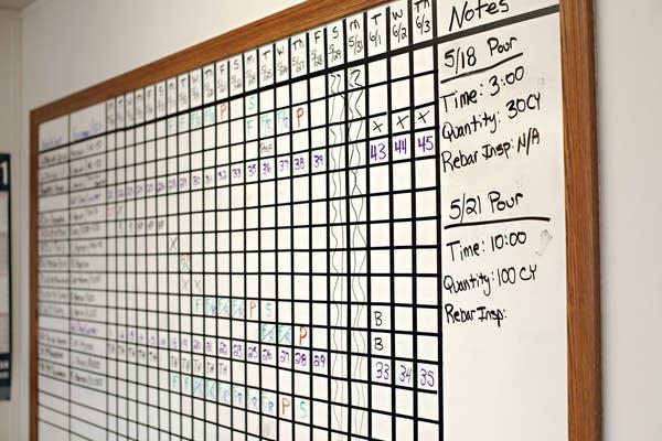 A white board shows a calendar in a grid layout.