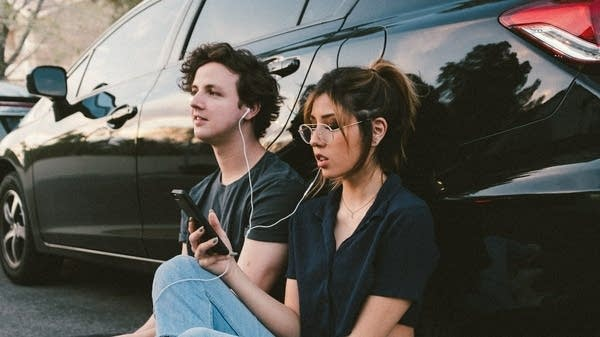two people listening to recorded music