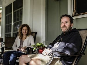 Joe McLean relaxes on his front porch with his wife, Colleen, behind him.
