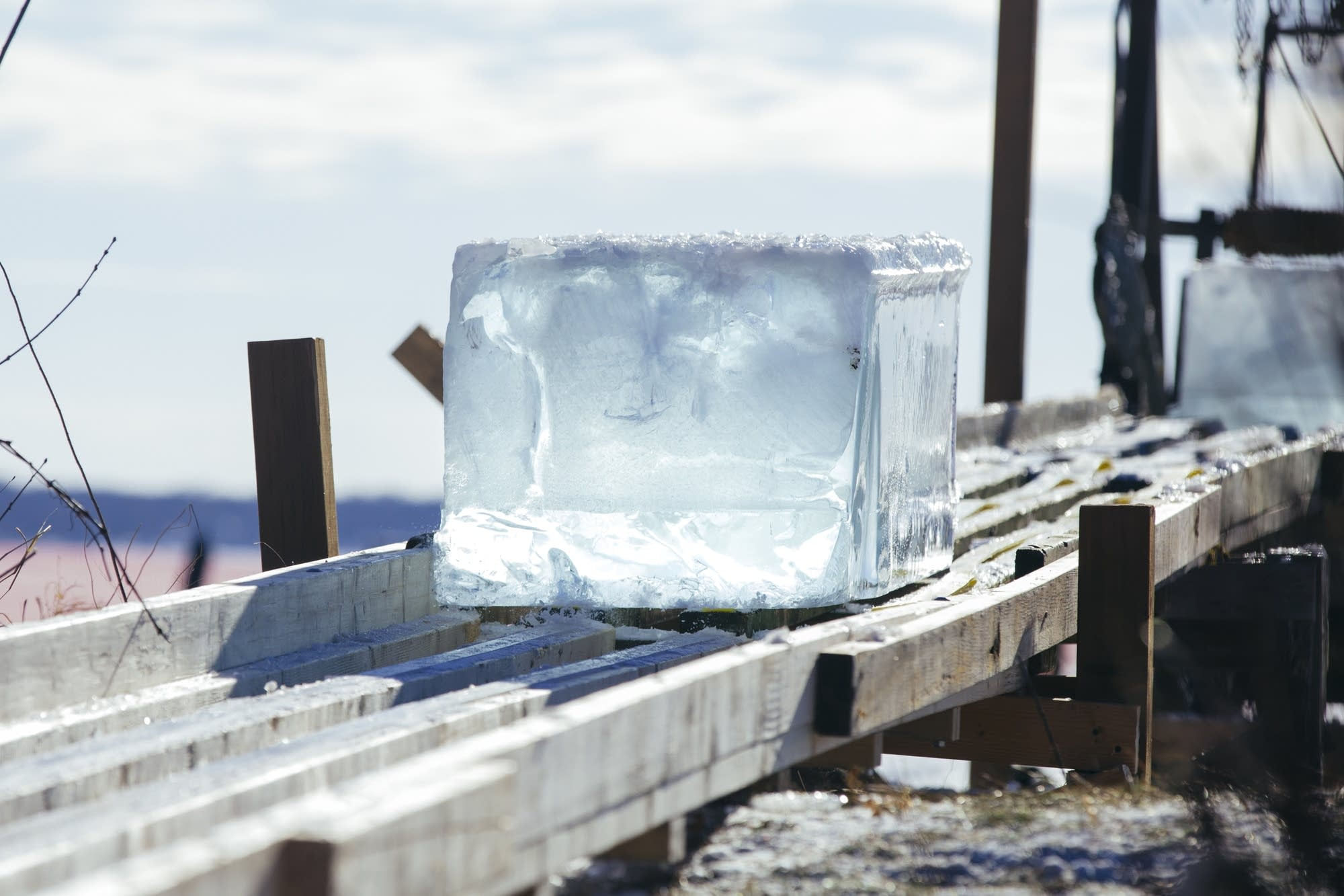 An ice block slides down a wooden ramp.