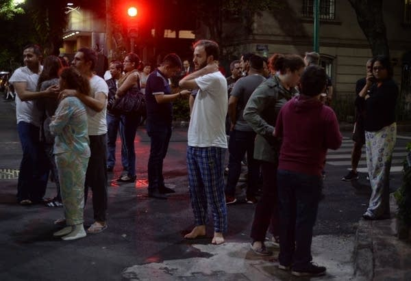People gather on a street in downtown Mexico City during an earthquake.