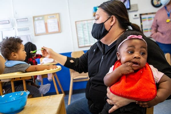 A woman in a mask feeds two babies.