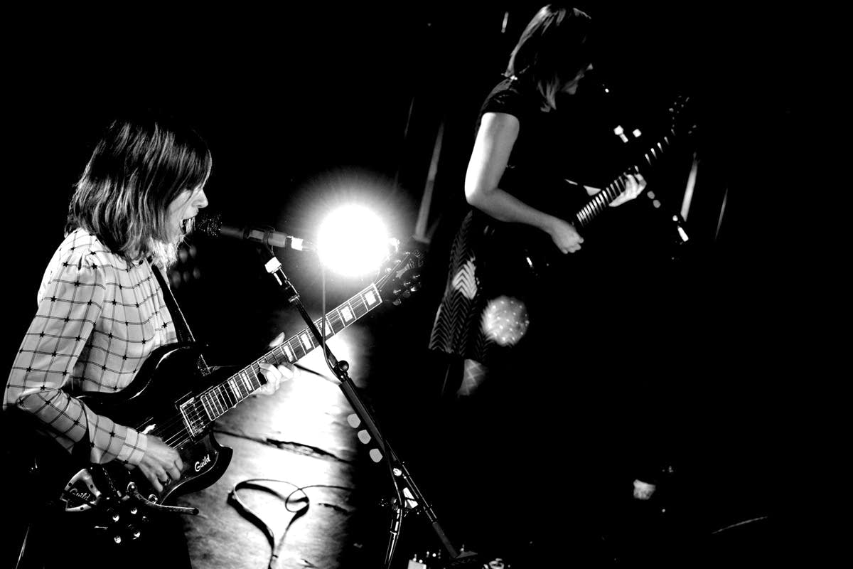 Carrie Brownstein and Corin Tucker standing on stage playing guitars.