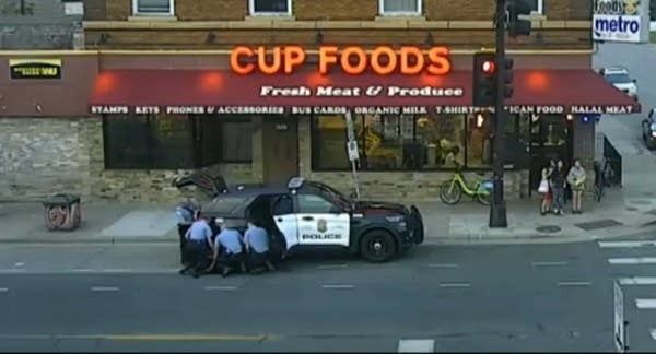 A surveillance video showing police making an arrest outside a store.