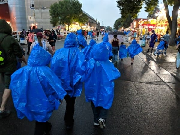 Fairgoers don their ponchos as a storm rolls over