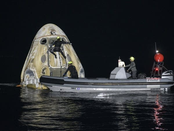 A recovery crew checks on a spacecraft