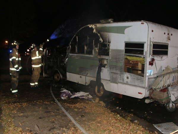 St. Paul firefighters inspect a fire-damaged camper
