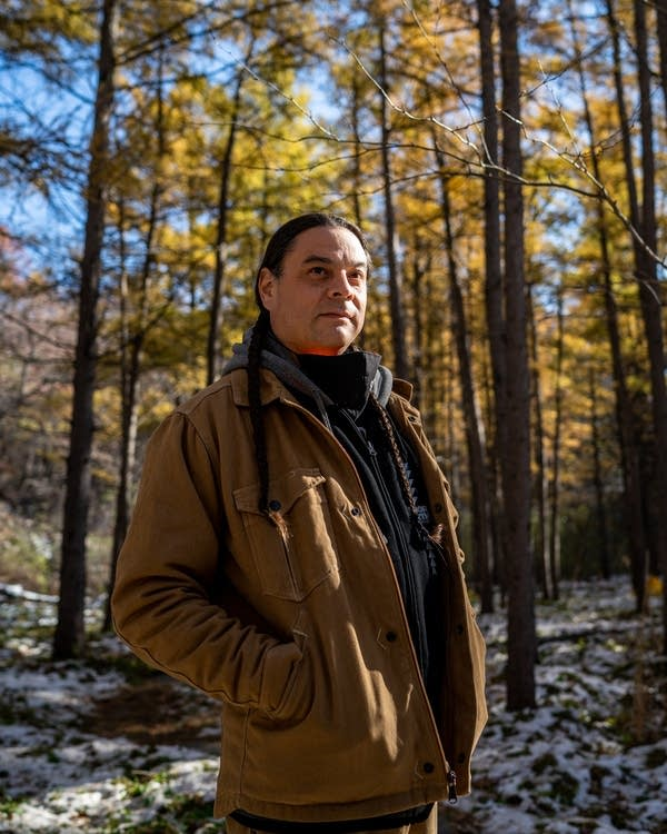 A man in a beige jacket stands in a yellow forest.