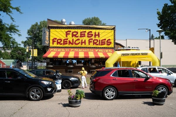 Cars line up in front of a french fry stand.