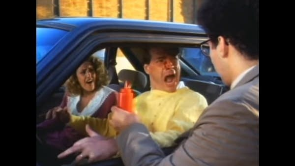 """Still from """"Brain Donors"""" film: Man in car squirted w/ Ketchup"""