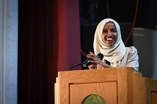 U.S. Rep. Ilhan Omar smiles at a podium on stage.