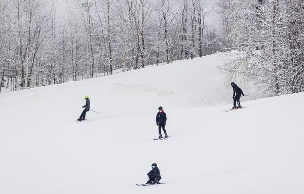 People ski and snowboard down a slope