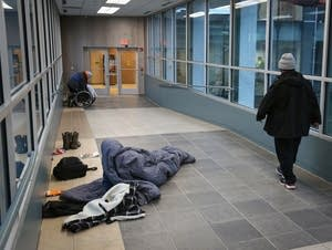 Two people gather their belongings after sleeping the night in the skyway