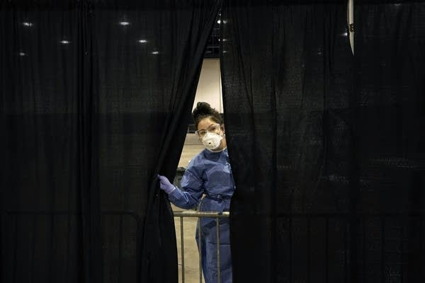 A medical professional peeks through a curtain.