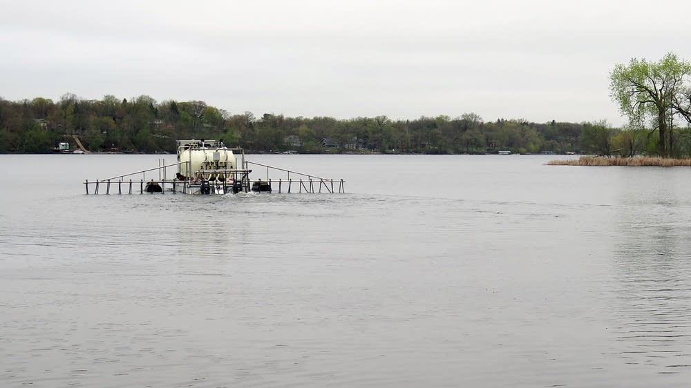 A barge deposits liquid alum in Bald Eagle Lake.