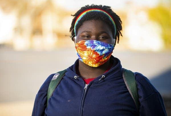 Person wearing tie-dye mask.