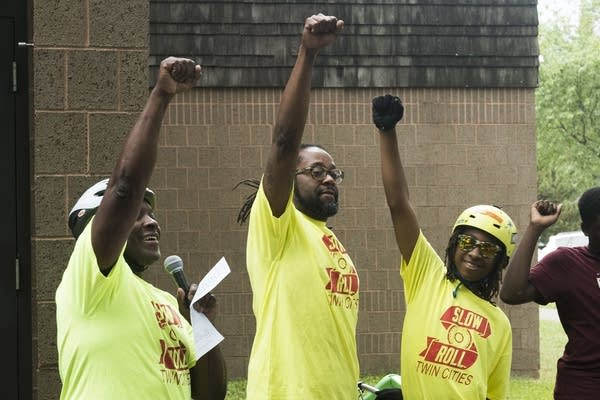 Slow Roll leaders throw their fists in the air.