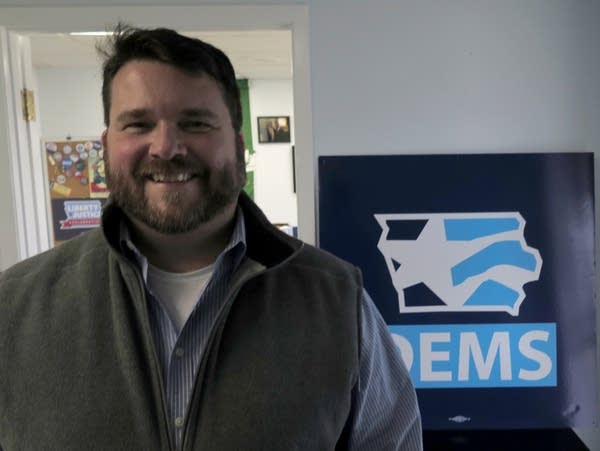 A man stands in front of a Iowa Democrats sign.
