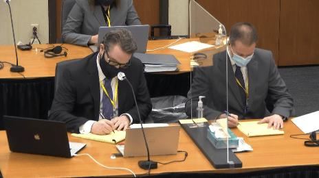 Two men sit behind a desk.