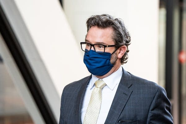 A man in a suit and a blue mask.