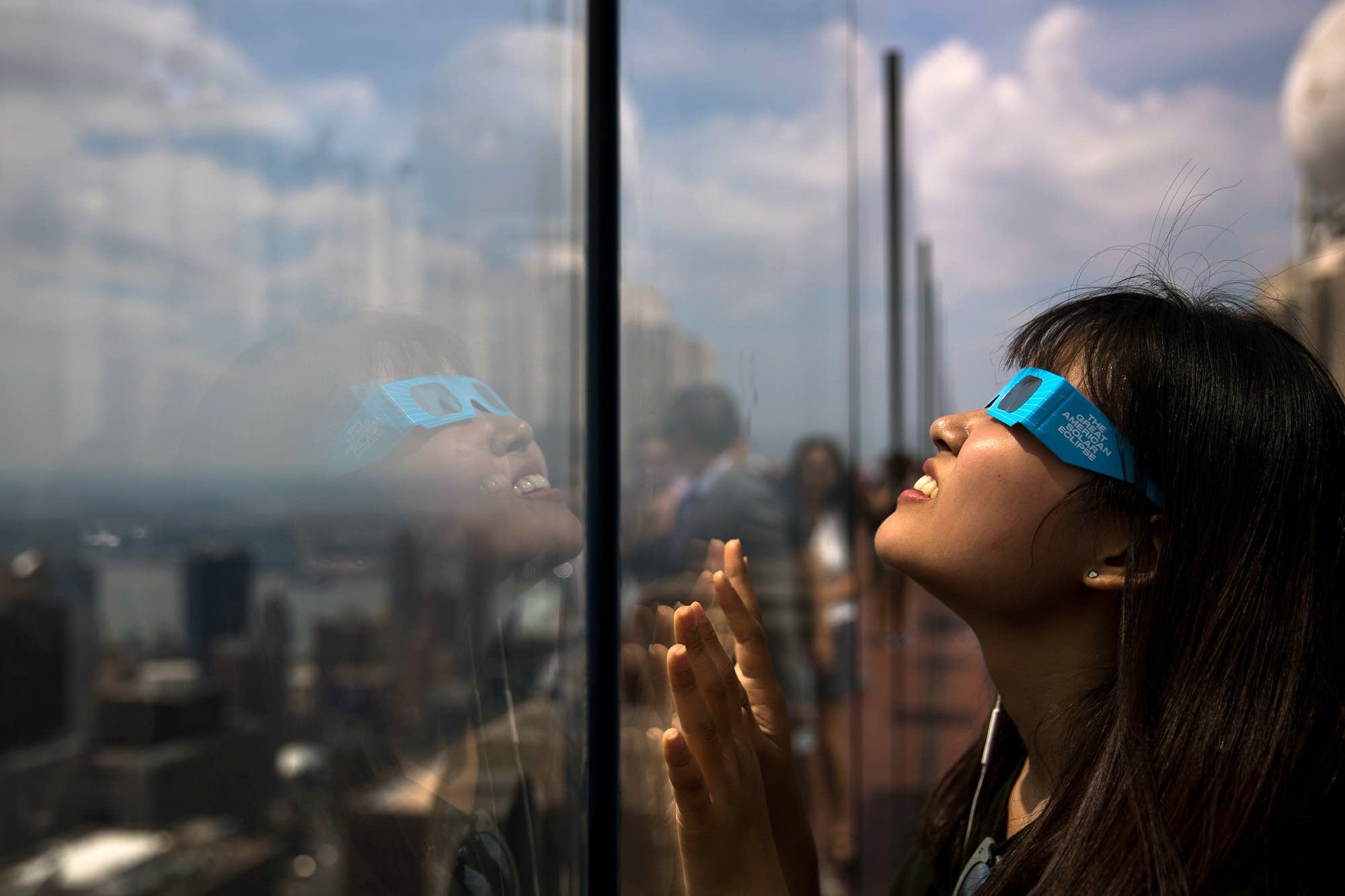 A woman views the solar eclipse at Rockefeller Center in New York City.