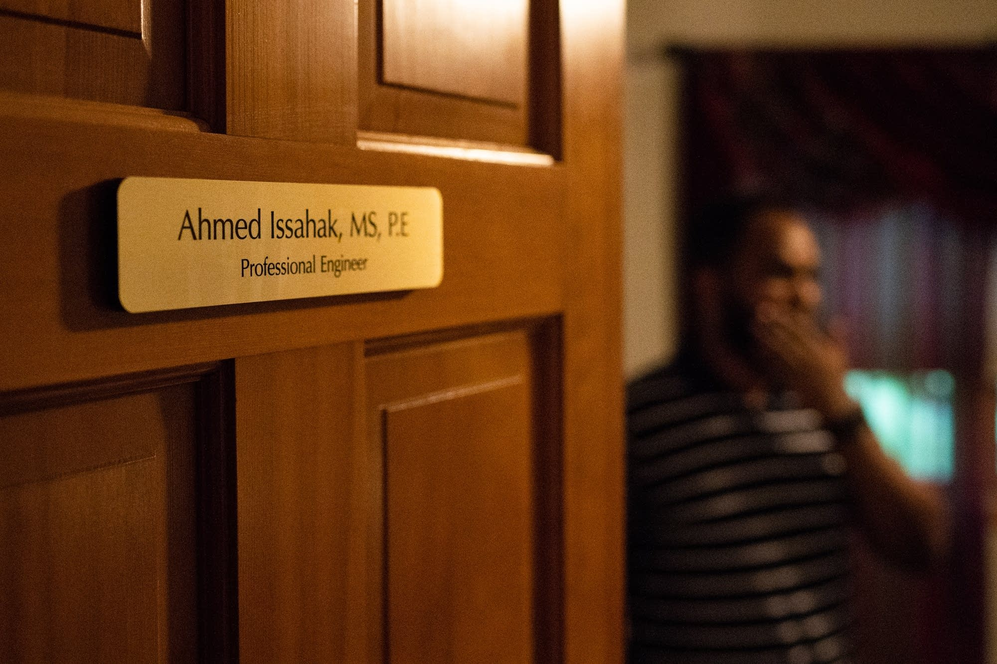 Ahmed Issahak stands in his home office in Brooklyn Park, Minn.