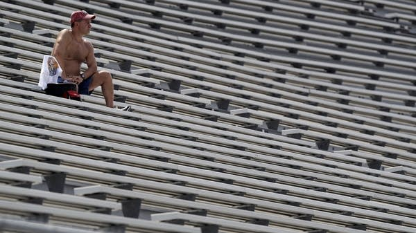 A fan watches NASCAR from the stands during a heat wave
