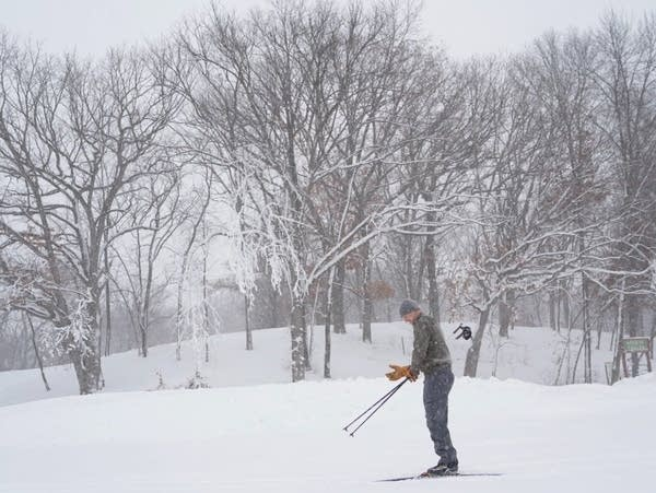 A man puts his gloves on before skiing.