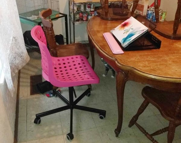 A pink desk chair and laptop sits at a dining room table.