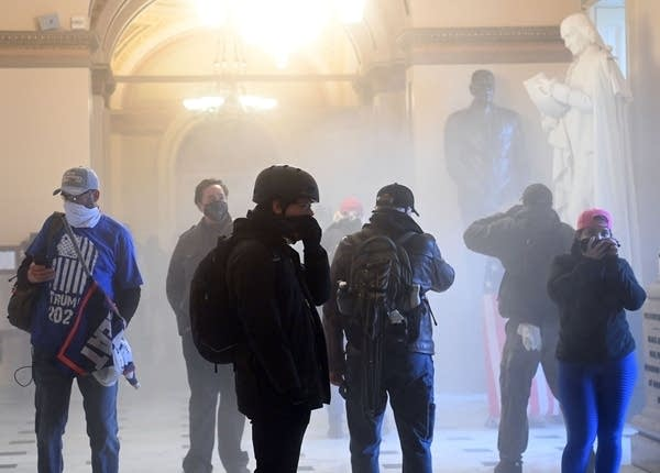 Trump supporters enter the U.S. Capitol as tear gas fills the corridor.