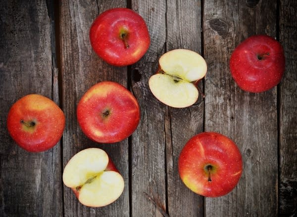 A collection of apples, some cut in half, sit on a wooden backdrop.