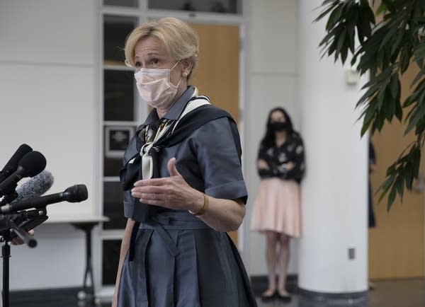A person wearing a face mask gestures while speaking at microphones.