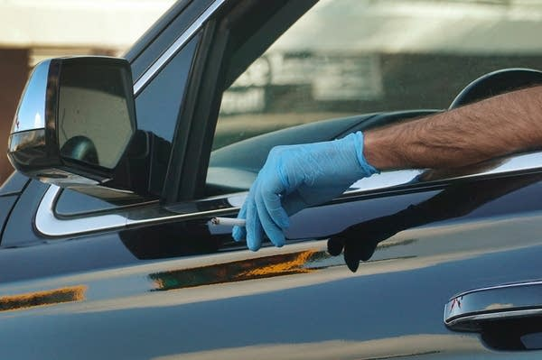 A person holds a cigarette out of a car window while wearing a glove.
