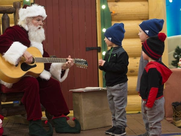 Kurt Martell plays Jingle Bells on guitar as three brothers sing along.