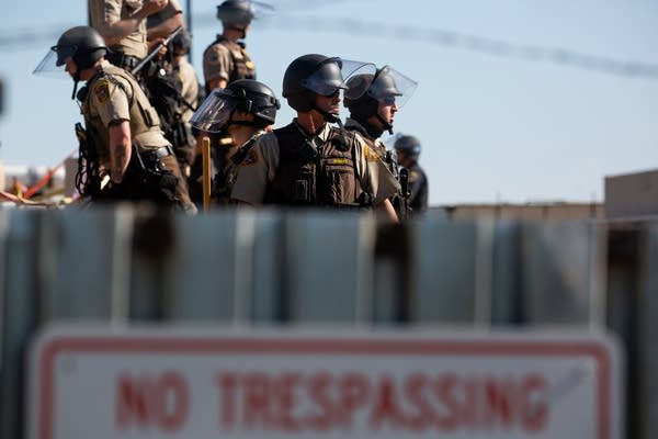"""Police stand behind a steel wall with a """"No Trespassing"""" sign in front."""