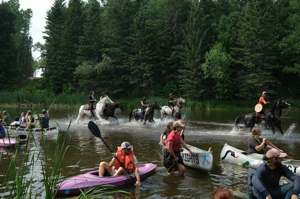 Demonstrators on horseback and in canoes gather at a river.