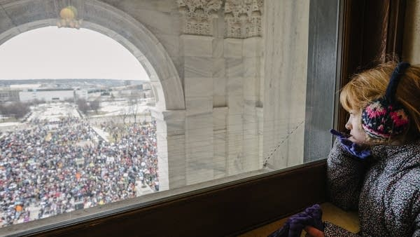 Seven-year-old Penny Peterson looks out the window of the State Capitol.
