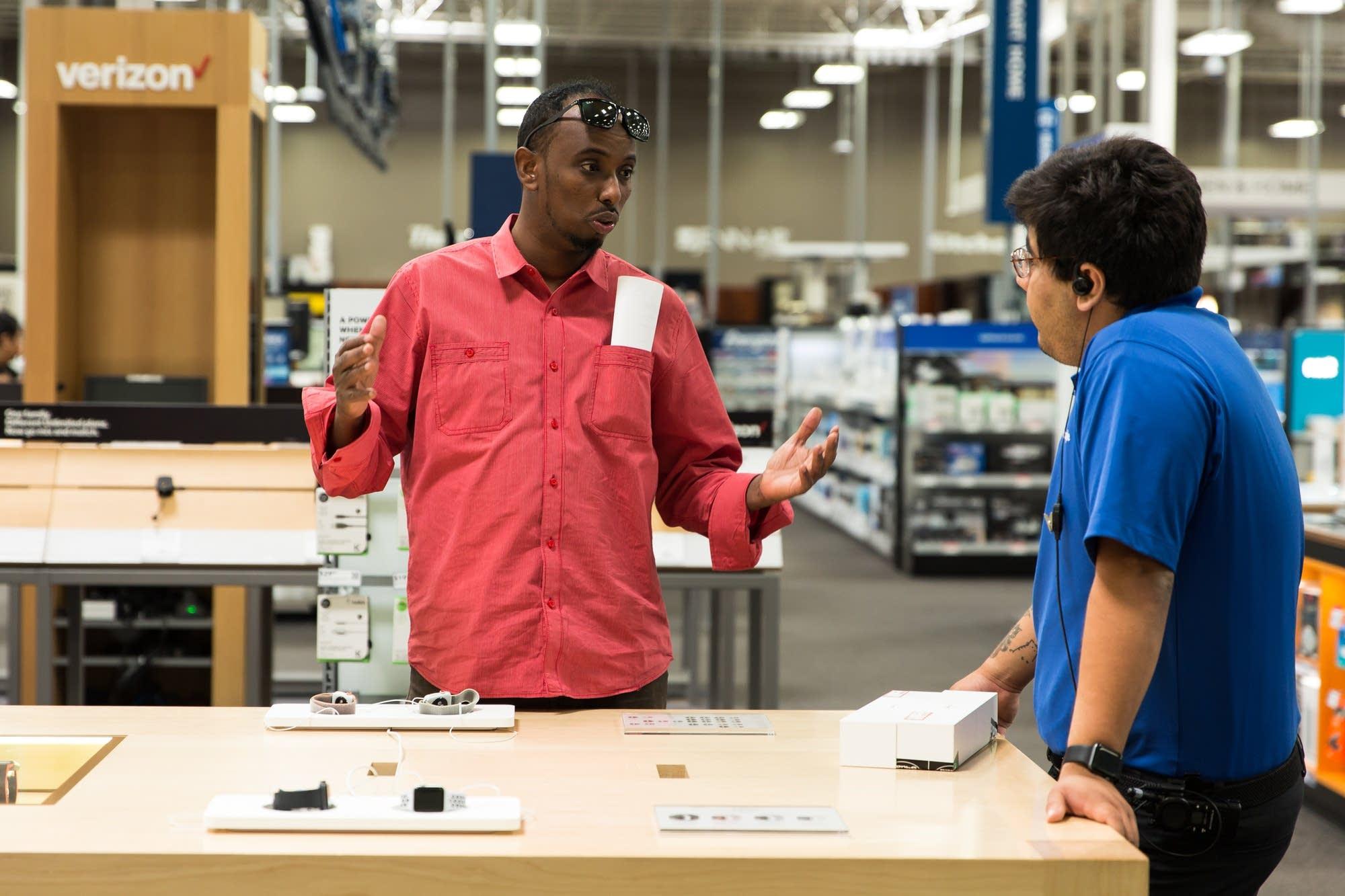 Abdifatah Mohamed asks Best Buy employee Darryn Regalado a question.
