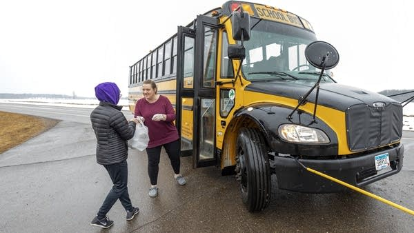 A person standing outside a school bus hands a bag to a child.