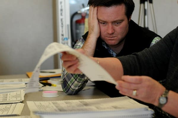 A Coleman representative watches the recount