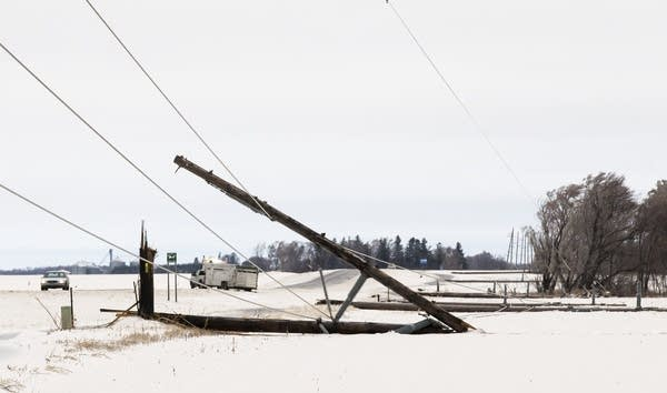 A row of power line poles are snapped from ice and wind along Highway 56.