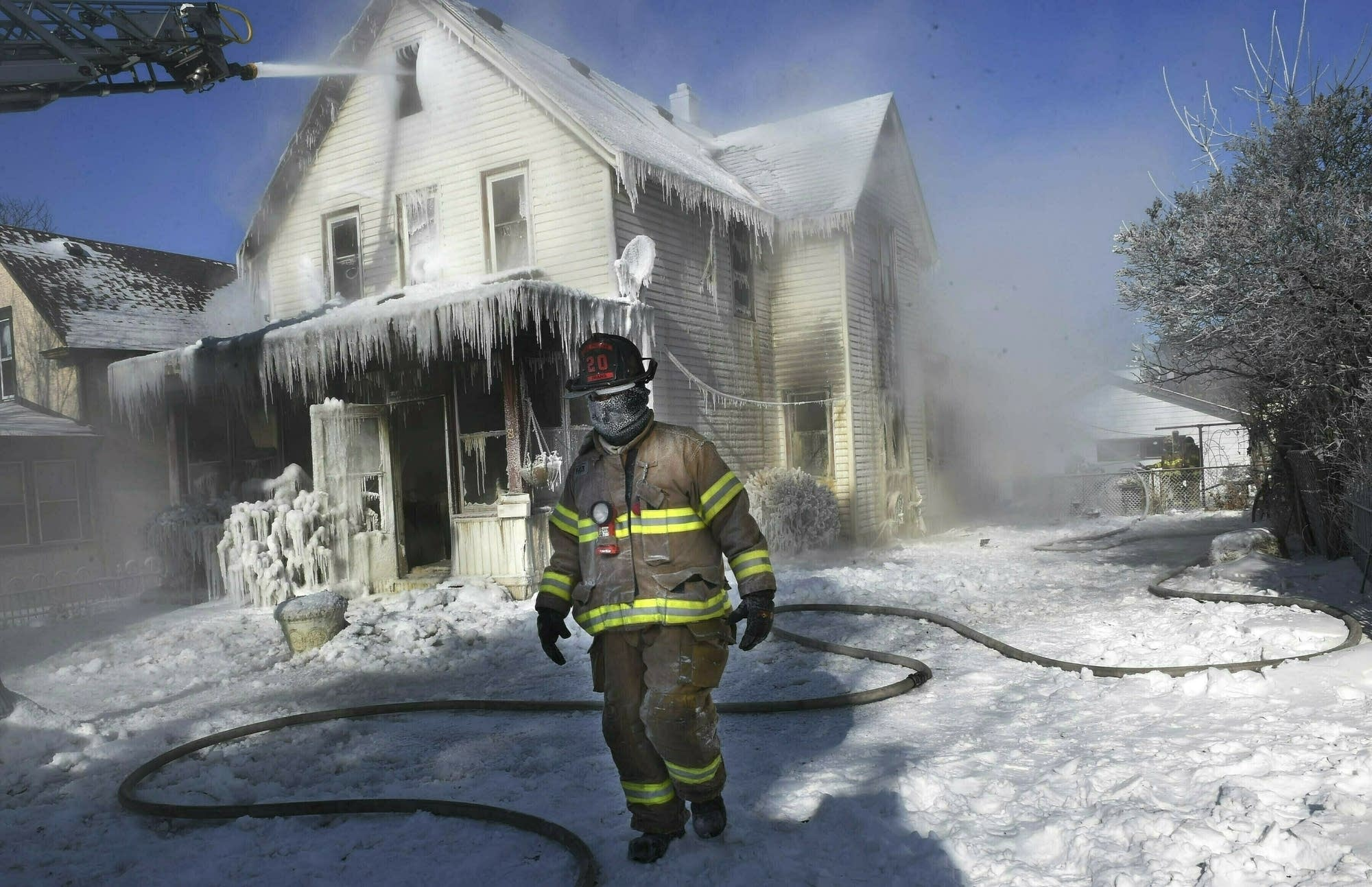 A firefighter walks past an ice-encrusted home