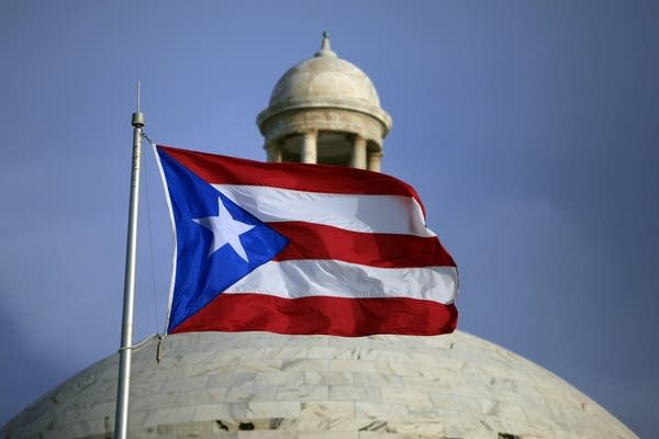 The Puerto Rican flag flies in front of Puerto Rico's Capitol.