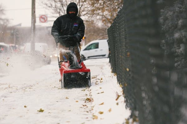 A man clears snow, ice and leaves from the sidewalk in Minneapolis.