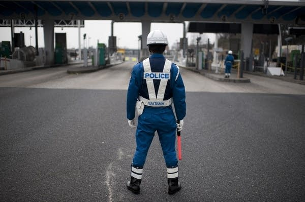 A policeman controls the highway in Japan