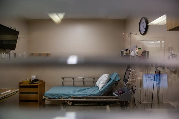 A hospital bed sits behind a curtained window.