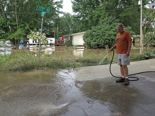 Gary Timp washes mud off his sister's driveway.